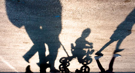 quite time: Blurry silhouettes and shadows of a familly walking with two kids, one on a small three wheels bike, upside down