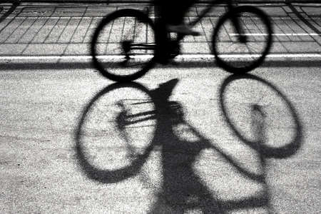 quite time: Blurry silhouette and shadow of a cyclist on a proteted bike path in sunset in black and white Stock Photo