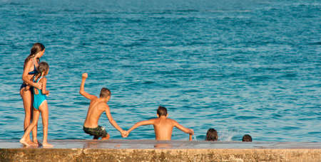 Vodice, Croatia - August 21, 2016: Two young girls watching four pre-adolescent boys holding hands while jumping into the sea from the pier.