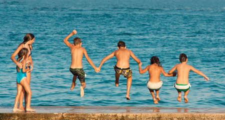 Vodice, Croatia - el 21 de agosto de 2016: Dos muchachas que miran a cuatro muchachos pre-adolescentes que toman de las manos mientras que saltan en el mar del embarcadero.