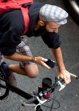 Belgrade, Serbia - July 26, 2016: A man looking at the mobile phone while riding his bike in a busy street