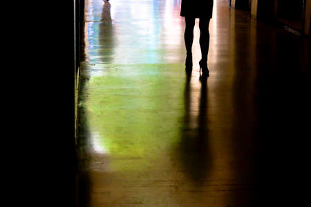 Blurry silhouette and shadow of a woman standing alone, from waist down,  in the alley in the night in city centre Stock Photo