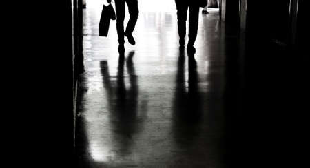 Two people silhouettes and shadows in the city passage in black and white