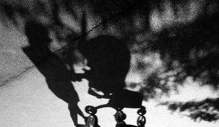 Verschwommener Schatten einer Frau mit postpartaler Depression, die einen Kinderwagen auf der rissigen Asphalt-Vorstadtparkstraße in Schwarzweiss schiebt