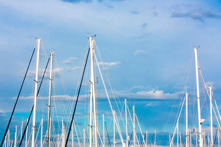 Sailing boat masts and the blue sky with white clouds