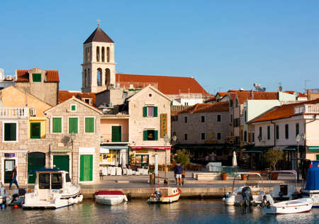 Vodice, Croatia - August 22, 2017: Sunny morning in small Mediterranean town square with stone houses and old church tower. with moored boats on the dock, and few people walking by