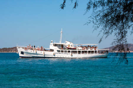 Island Prvic; Croatia - August 25, 2017 : Ship Tijat from Jadrolinija with passengers - tourists embarked,  near island Prvic, seen through the branches of Mediterranean pine. This ship is operating daily between Sibenik and Vodice, with few stops on near