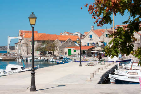 Sepurine, island Prvic, Croatia -  August 25, 2017: An easy going summer day in small Mediterranean  village with stone houses, pier with fishing boats moored, and few locals and tourists passing by