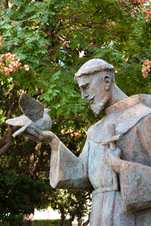 Sibenik, Croatia - August 18, 2017: Public statue of Saint Francis of Assisi holding a dove and a cross, in the park next to the church of Our Lady out of town in Sibenik, Croatia Zdjęcie Seryjne - 110497902