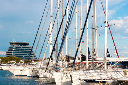 Vodice, Croatia - August 12, 2017: Sailing boats anchored in marina and luxury hotel Olympia Sky behind them
