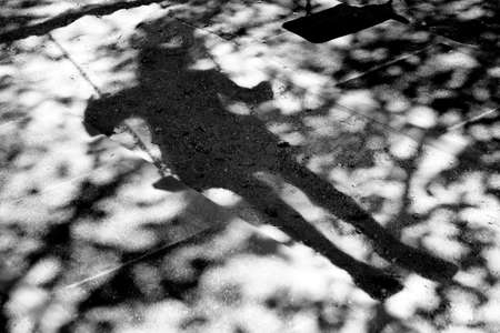 Bluury shadows of a teen person on a swing and a tree branch