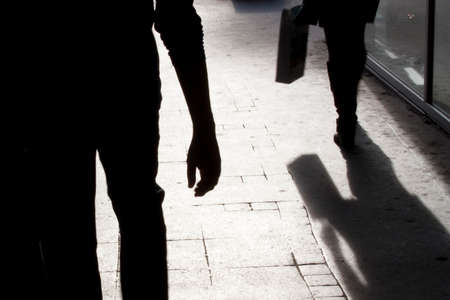 Verschwommene Silhouette und Schatten einer Frau, die eine Tasche trägt, und eines Mannes, der ihr folgt, in der Nacht auf der Stadtstraße