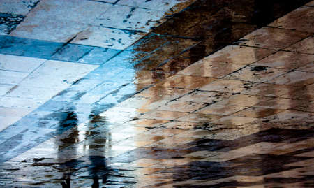 Blurry reflection shadow of a two people walking in the old ruined city pedestrian zone just after the rain