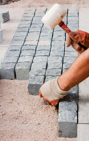 Hands in gloves of a builder worker laying on the granite cobblestone sett on sand with rubber mallet hammer , and paving street sidewalk on construction site Foto de archivo