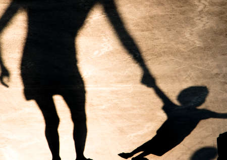 Sombras siluetas de madre e hijo desobediente tirando de su mano en el paseo de verano en blanco y negro sepia