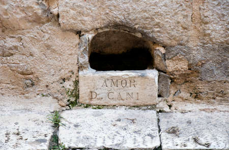 Watering hole , stone made bowl in the facade wall of house in old town Sibenik main street, with latin sign AMOR D CANI , was man-made to provide drinking water for dogs ( and cats ) and is regularly filled with fresh water