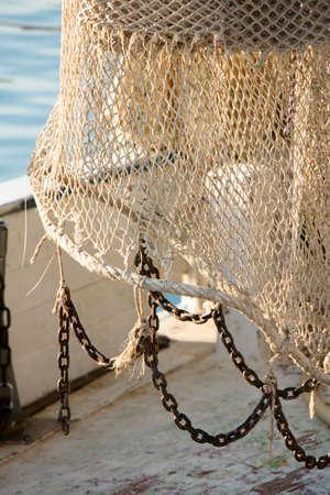Fishing trawl net hanging on a trawler boat deck Фото со стока