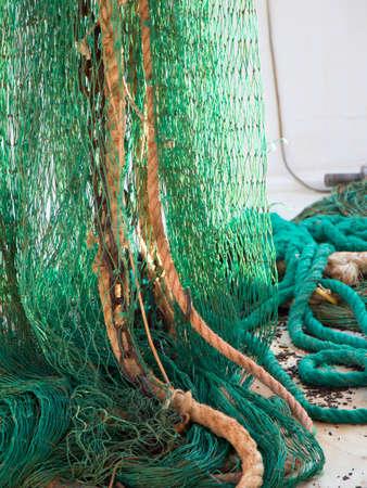 Green fishing trawl net henging on a trawler boat deck Фото со стока