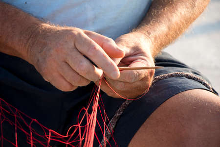 Fisherman hands repairing his red fishing net with needle , close up detail Фото со стока