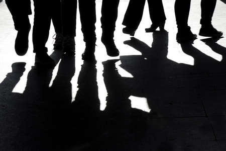 High contrast blurry silhouettes and shadows of legs of  people walking  免版税图像
