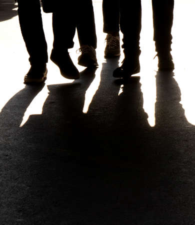 Blurry silhouettes and shadows of legs of  three people walking, in black and white