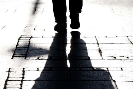 High contrast blurry silhouette shadow of a person legs walking on city street sidewalk in black and white