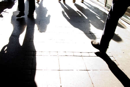 High contrast silhouette shadows of people walking on city street in motion blur black and white 免版税图像