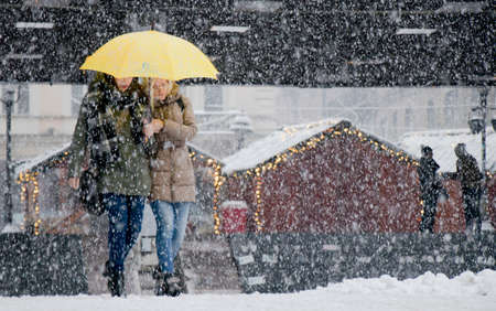 Belgrade, Serbia - December 15, 2018: Two young women walking under umbrella in heavy snowfall in city street with decorated Christmas stands in he background 新闻类图片