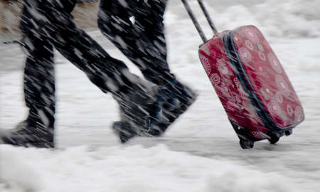 Winter travel; Blurry legs of two young people walking fast in heavy snowfall and rolling red wheeled suitcase 免版税图像