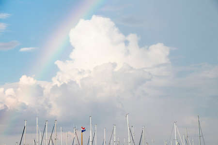 Cloudy sky with rainbow over sailing masts and pole with a Croatian flag