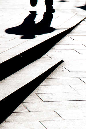 Blurry silhouette shadow of a man walking on a city sidewalk with steps  in black and white high contrast 免版税图像