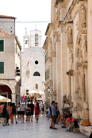 Sibenik, Croatia - August 6, 2018: People walking in front of the St James Cathedral and St Barbara church