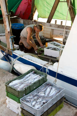 Tribunj, Croatia - August, 24, 2018: Fisherman sorting out the catch on a deck of a moored trawler boat 新闻类图片