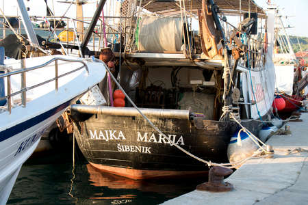 Tribunj, Croatia - August 24, 2018: Fishing boat Majka Marija Sibenik, with equipment for traditional commercial fishing techniques in Adriatic sea, moored at pier 新闻类图片