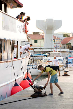 Vodice, Croatia - August 11, 2018: A cruise ship Carpe Diem arriving in Vodice and  docking. A man and a teenage boy on a pier fastening the ship ropes on a bollard while  passengers watching