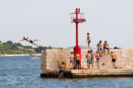 Vodice, Croatia - August 2, 2018: Young men in swimsuits standing on the pier and watching a man jumping in the sea in summer season