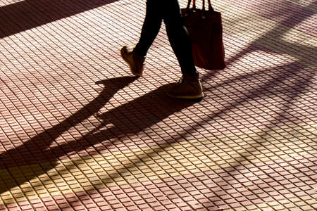 Blurry silhouette shadow of legs of a person carrying a bag while walking on tiled street sun lighted sidewalk