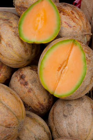 Bunch of organic cantaloupes, and one cut in half showing its orange flesh, displayed on sale on farmer's market stand in Serbia, detail