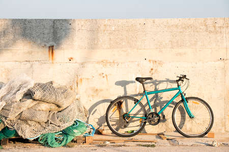 Bunch of old weathered trawl fishing nets and a parked bicycle on fishing village pier on a sunny day 免版税图像