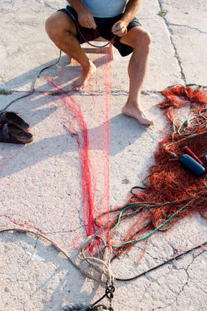 Fisherman reparing fishing net on the shore