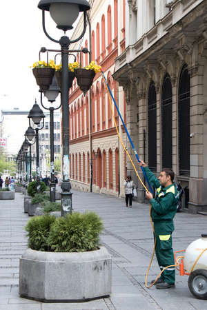 Belgrade, Serbia - April 9, 2019: City greenery service watering flowers in baskets on light poles in pedestrian street 新闻类图片