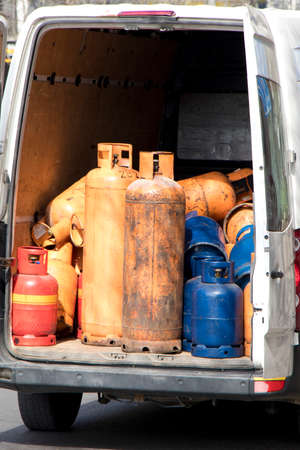 Different color and size cylinder gas bottles in a parked delivery van trunk for refill and supply 免版税图像