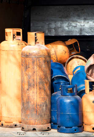 Different color and size cylinder gas bottles stored for refill and supply