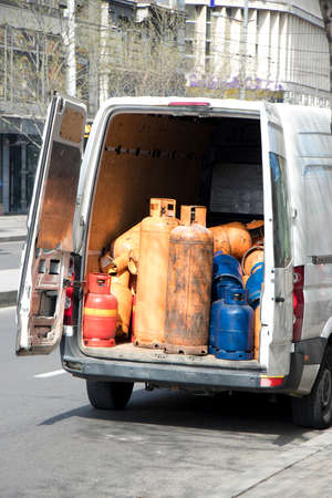 Different color and size cylinder gas bottles stored in a delivery van trunk for refill and supply 免版税图像
