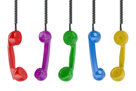 telephonic: Multi colored handset in the row isolated on green background Stock Photo