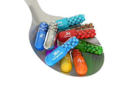 Capsules with Mn, Ca, K, Se, Zn, Cu, Fe, Mg, I, Na element dietary supplement in the spoon, 3D rendering isolated on white background