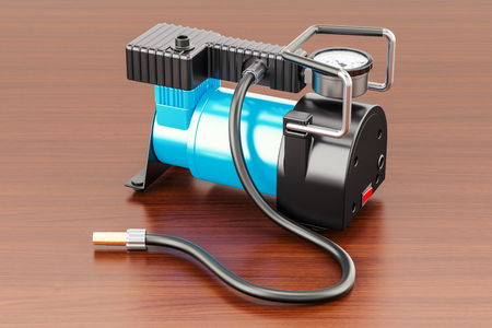 Car portable electric air compressor on the wooden table. 3D rendering