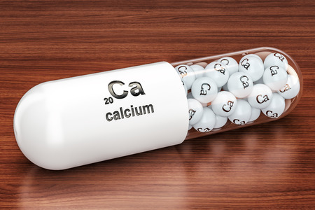 Capsule with Calcium Ca element on the wooden table. 3D rendering Archivio Fotografico