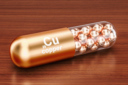 Capsule with copper Cu element on the wooden table. 3D rendering