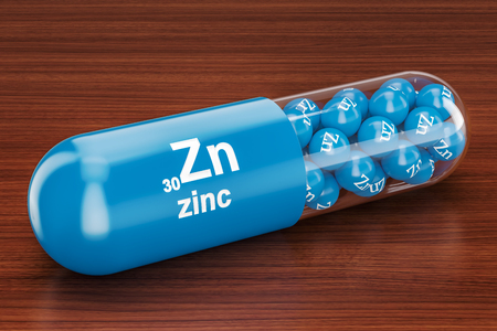 Capsule with zinc Zn element on the wooden table. 3D rendering Stock Photo